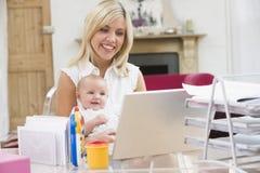 Madre joven con el bebé que trabaja de hogar imagenes de archivo