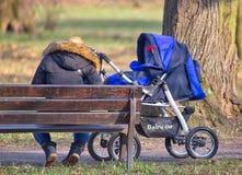 Madre joven con el cochecito de niño Imagen de archivo libre de regalías