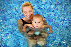 Madre joven con el hijo en una piscina Fotos de archivo libres de regalías