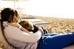 Madre joven con el hijo que descansa sobre costa de mar, familia feliz junto que habla, concepto de la gente de la forma de vida Imágenes de archivo libres de regalías