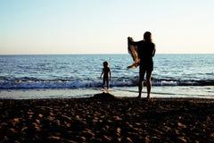 Madre joven con el hijo que descansa sobre la costa de mar, togethe feliz de la familia Foto de archivo