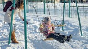 Madre joven con el niño que balancea en al aire libre determinado del oscilación en parque del invierno Nieve que cae, nevadas, i