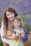 Madre joven con la hija joven que sonríe en el campo de la lavanda Hija que se sienta en las manos de la madre Muchacha en colori Fotos de archivo libres de regalías