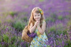 Madre joven con la hija joven que sonríe en el campo de la lavanda Hija que se sienta en las manos de la madre Muchacha en colori Imágenes de archivo libres de regalías