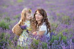 Madre joven con la hija joven que sonríe en el campo de la lavanda Hija que se sienta en las manos de la madre Muchacha en colori Imagenes de archivo