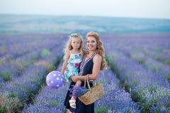 Madre joven con la hija joven que sonríe en el campo de la lavanda Hija que se sienta en las manos de la madre Muchacha en colori Fotos de archivo