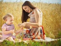 Madre joven con la hija linda en el campo de trigo Foto de archivo libre de regalías