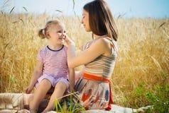 Madre joven con la hija linda en el campo de trigo Imagen de archivo