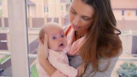 Madre joven con la hija minúscula en las manos almacen de video