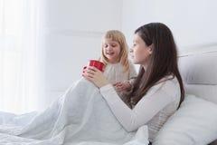 Madre joven con la hija que bebe algo de té mientras que se sienta en cama en el dormitorio blanco foto de archivo libre de regalías