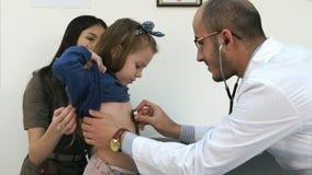 Madre joven con la muchacha que es examinada por el pediatra de sexo masculino con el estetoscopio almacen de video