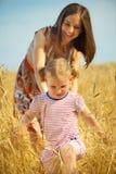 Madre joven con la pequeña hija en el campo de trigo Imagenes de archivo