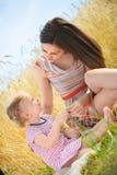 Madre joven con la pequeña hija en el campo de trigo Imagen de archivo