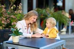 Madre joven con la pequeña hija que tiene comida en café del aire libre foto de archivo