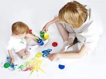 Madre joven con la pintura del bebé de la belleza en el fondo blanco imágenes de archivo libres de regalías