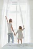 Madre joven con las cortinas de ventana de abertura de la hija fotografía de archivo libre de regalías