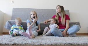 Madre joven con los niños que se sientan en la alfombra y la TV de observación almacen de metraje de vídeo