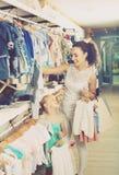 Madre joven con los pijamas de compra del bebé de la hija en la sección de los niños Fotografía de archivo libre de regalías