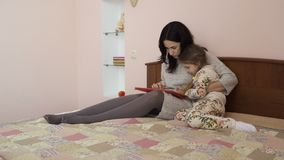 Madre joven con pequeña película adorable del reloj de la hija en la tableta que se sienta en cama almacen de metraje de vídeo