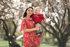 Madre joven con su bebé en brazos en jardín floreciente Imagenes de archivo