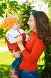 Madre joven con su bebé en parque Imágenes de archivo libres de regalías