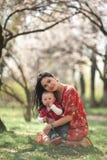 Madre joven con su bebé en paseo en jardín de la primavera Fotos de archivo libres de regalías