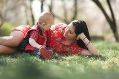 Madre joven con su bebé en paseo en jardín de la primavera Imagen de archivo