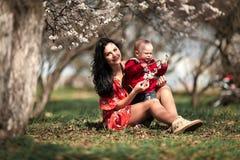 Madre joven con su bebé en paseo en jardín floreciente Fotos de archivo