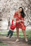 Madre joven con su bebé en paseo en jardín floreciente Imagen de archivo libre de regalías