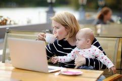 Madre joven con su bebé que trabaja o que estudia en su ordenador portátil Fotos de archivo