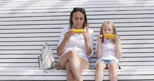 Madre joven con su hija que come maíz hervido en el parque en verano almacen de video