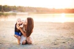 Madre joven con su hijo en la playa en un fondo de la puesta del sol Imagenes de archivo