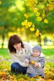 Madre joven con su pequeño bebé en el parque del otoño Imagen de archivo libre de regalías