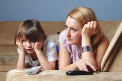 Madre joven con su reloj TV, cara triste del hijo Imagen de archivo libre de regalías