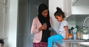 Madre joven con un hijab que bebe un vaso de agua cerca de su hija en la cocina 4k metrajes