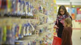 Madre joven con un niño dentro del supermercado que elige mercancías La niña señala el finger en algo y la mamá