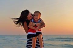 Madre joven con una pequeña hija que juega en la playa imagen de archivo libre de regalías