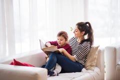 Madre joven con una pequeña muchacha en casa, leyendo un libro Imágenes de archivo libres de regalías