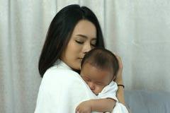 Madre joven de Asia con un bebé Fotografía de archivo
