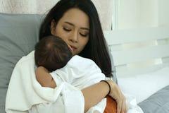 Madre joven de Asia con un bebé Fotos de archivo