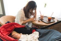 Madre joven de Asina que usa smartphone mientras que su bebé que juega en el cochecito de bebé foto de archivo libre de regalías