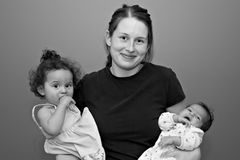 Madre joven de dos con sus manos llenas Foto de archivo