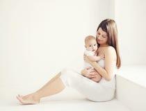 Madre joven de la foto suave de la comodidad con el bebé en casa en el sitio blanco Fotos de archivo libres de regalías