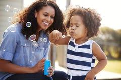 Madre joven de la raza mixta y burbujas que soplan de la hija afuera imagenes de archivo
