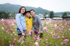 Madre joven de moda y sus niños de dos adolescentes que presentan feliz por el campo de flores Imágenes de archivo libres de regalías