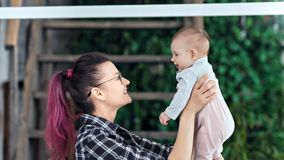 Madre joven del inconformista feliz de la vista lateral que juega con poco hijo que lo admira y que besa primer medio almacen de metraje de vídeo