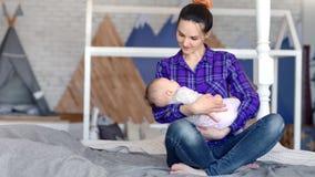 Madre joven del inconformista feliz que disfruta de la maternidad que calma poco tiro lleno del bebé lindo metrajes