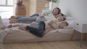 Madre joven del retrato con sus hijos adolescentes que duermen junto en la cama grande Un muchacho que se sienta en la silla Amor almacen de metraje de vídeo