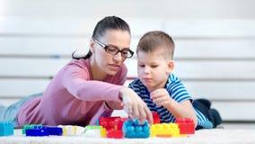 Madre joven despreocupada del primer medio que juega los cubos del constructor con poco hijo lindo almacen de metraje de vídeo