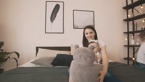Madre joven e hija linda que se divierten en dormitorio, cámara lenta almacen de metraje de vídeo